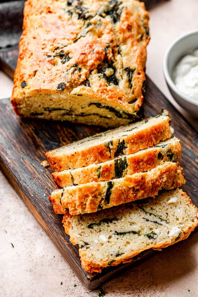 top shot of sliced spinach and feta bread set on top of a dark cutting board