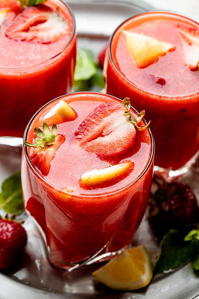 strawberry sangria in short drinking glasses topped with strawberry slices and lemons