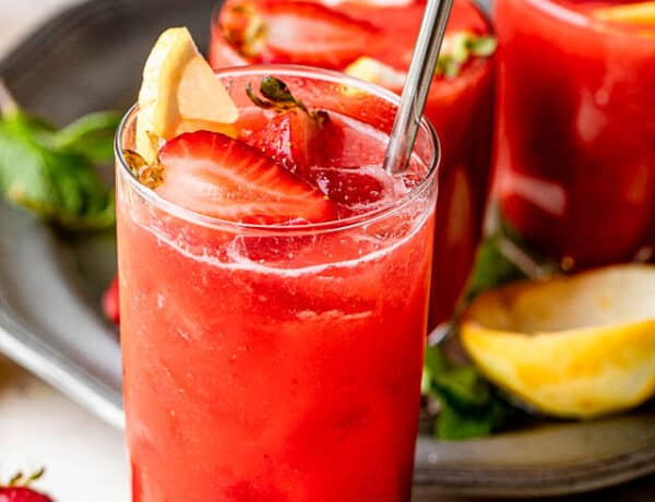strawberry lemonade sangria in a tall glass and topped with strawberries and lemons