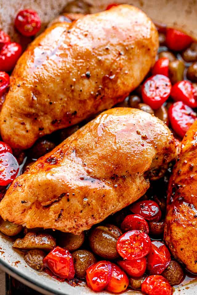 chicken breasts set over a bed of cherry tomatoes and small potatoes