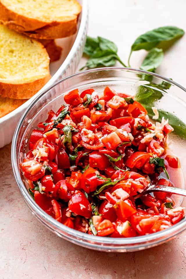 tomato salad in a salad bowl set next to toasted garlic bread