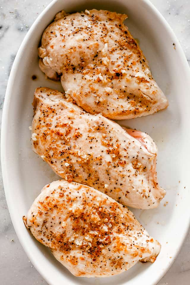 top view of seasoned chicken breasts in a white oval baking dish
