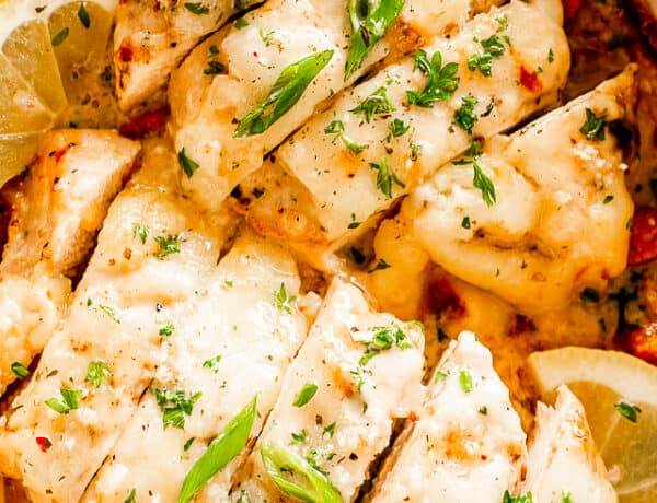 close up shot of sliced baked chicken breasts topped with caesar dressing and parsley