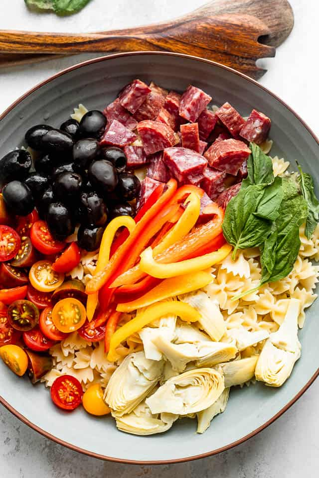 wooden spoons next to a salad bowl with arranged olives, salami, pasta, cheese, artichokes, tomatoes, basil leaves, and peppers