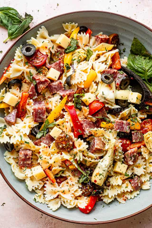 top view of a large blue salad bowl with pasta, olives, cheeses, and salami