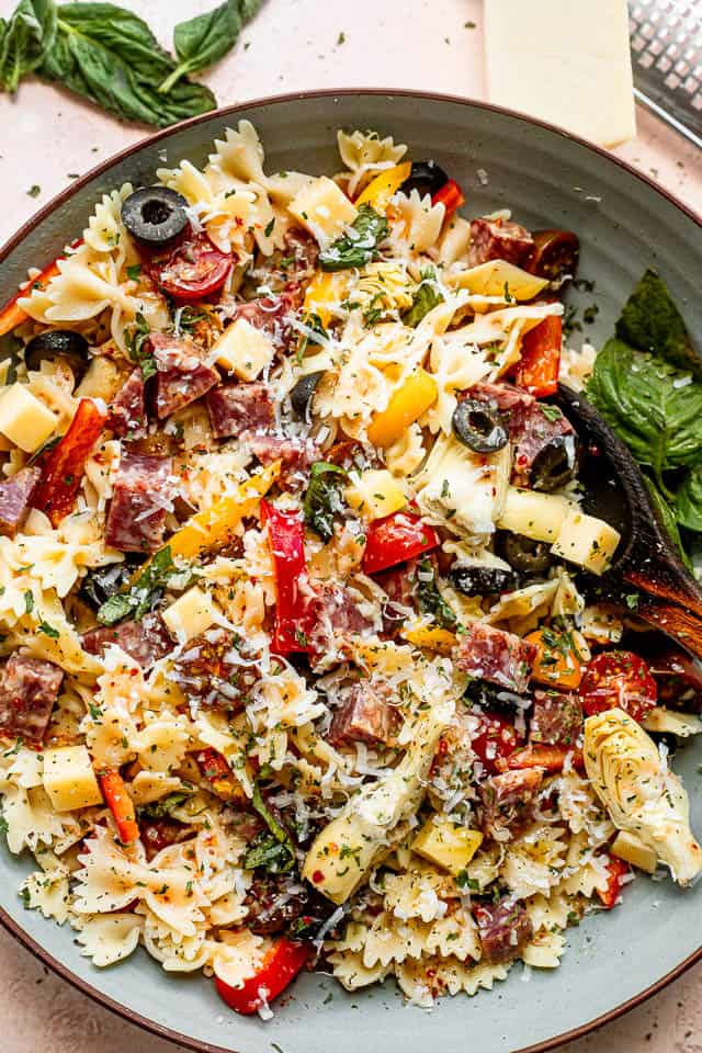 top view shot of a wooden spoon in a bowl filled with pasta, cheese cubes, salami cubes, tomatoes, and olives
