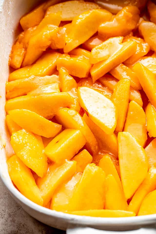 sliced peaches in a baking dish prepped for a peach cake