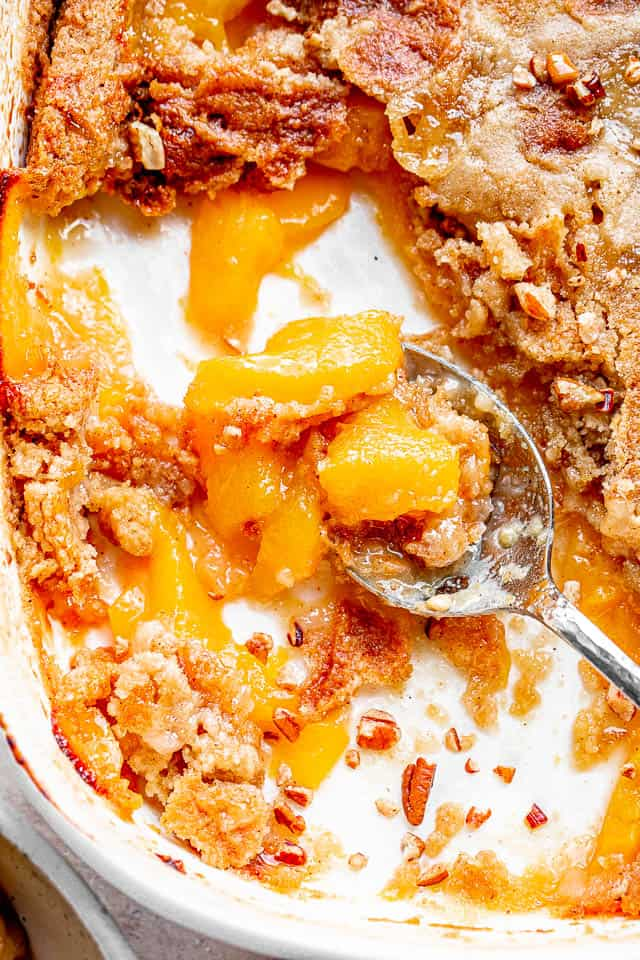 top shot of silver spoon scooping out a peach cake from white baking dish