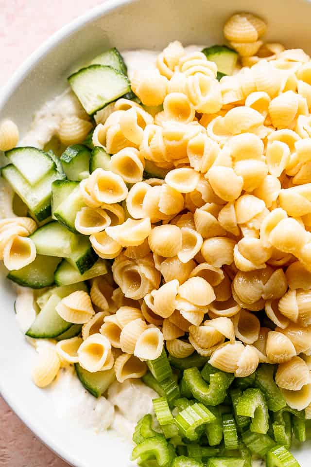 small pasta shells set over diced cucumbers and celery in a white bowl