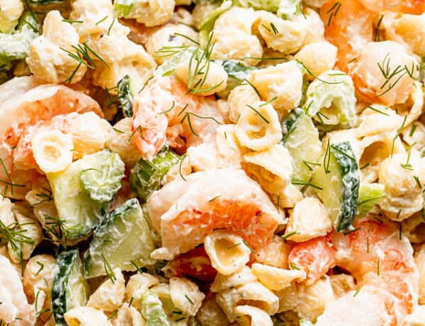 close up top shot of Creamy Shrimp Pasta Salad studded with sliced cucumbers and plump shrimp