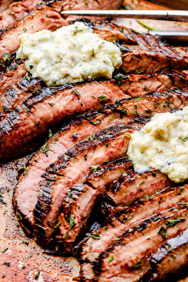 close up side shot of sliced flank steak topped with compound butter