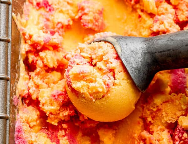 close up shot of mango strawberry frozen yogurt in a loaf pan with an ice cream scoop
