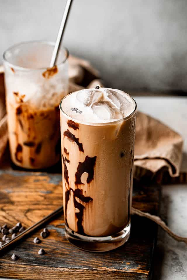 top side view of two drinking glasses filled with iced coffee and set on top of brown board