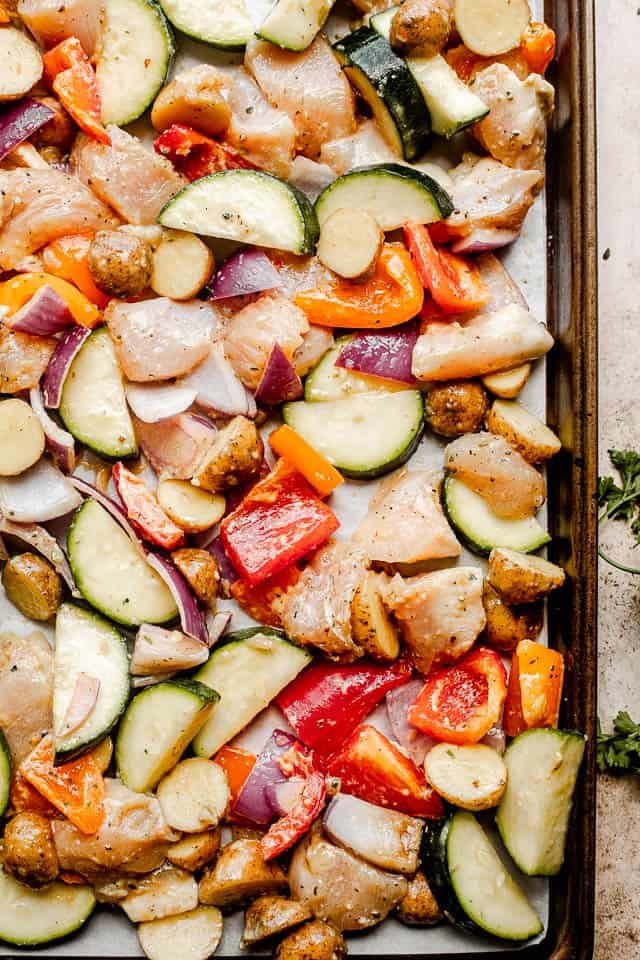 prepping raw chicken and vegetables on a baking sheet