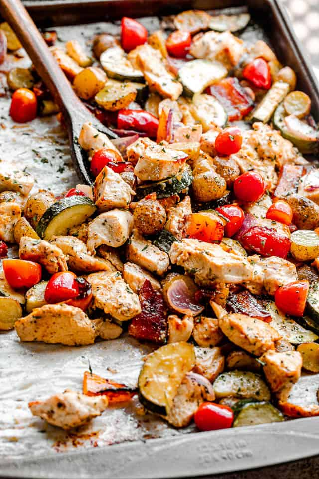 side view of mixing chicken and vegetables on a baking sheet with a brown wooden spoon