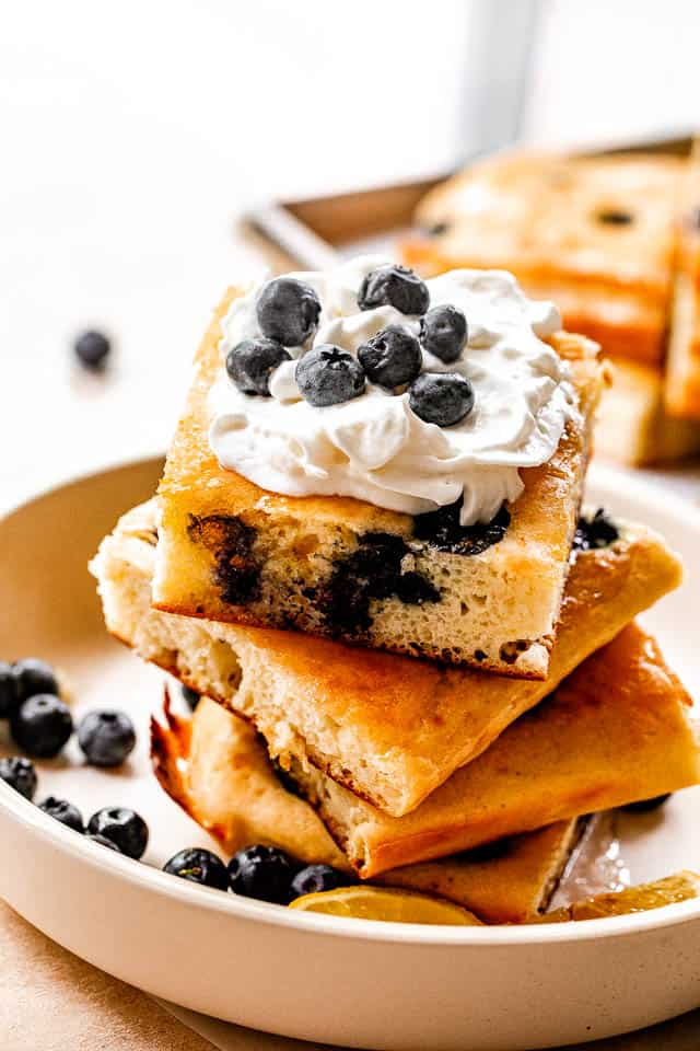 side shot of stacked sheet pan pancakes topped with whipped cream and blueberries