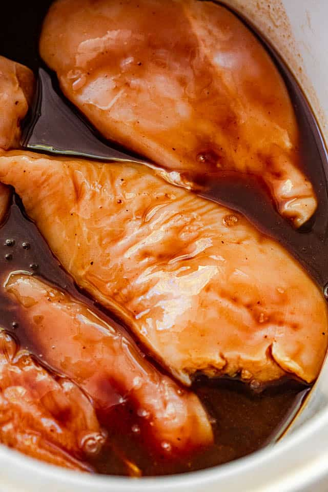 raw chicken breasts covered in barbecue sauce