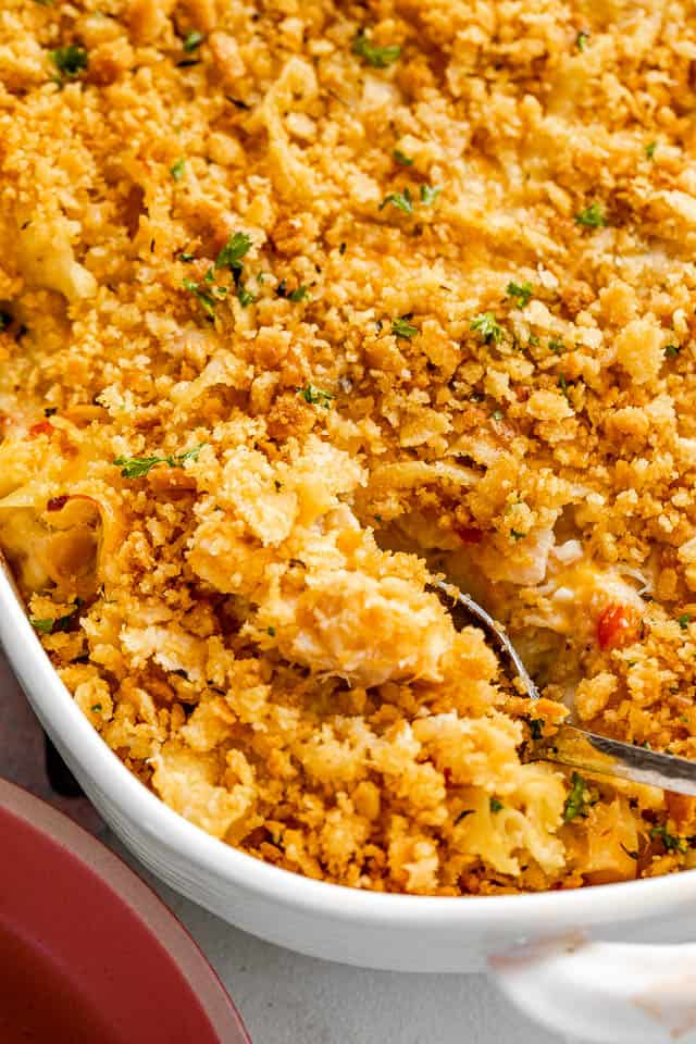 silver spoon cutting into a tuna noodle casserole topped with ritz crackers