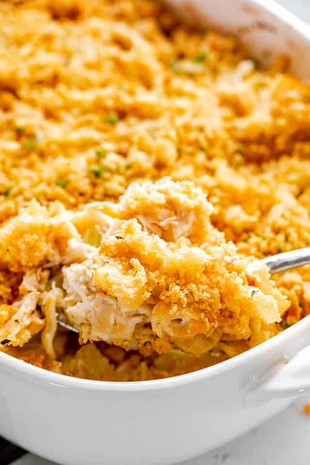 scooping out tuna noodle casserole from baking dish