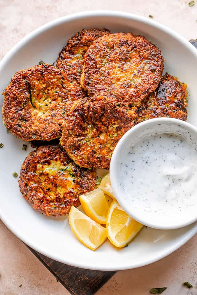 top shot of zucchini cakes in a white bowl with lemon wedges and dip