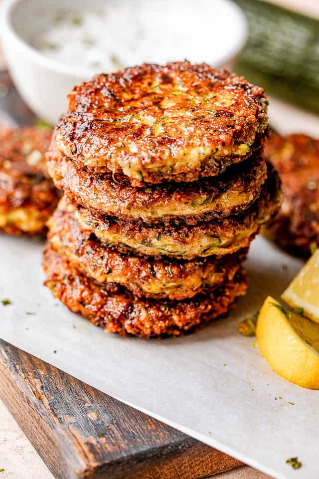stacked zucchini patties with lemon wedges next to them and yogurt dip behind