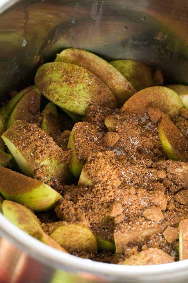 apple wedges in instant pot insert sprinkled with brown sugar and cinnamon