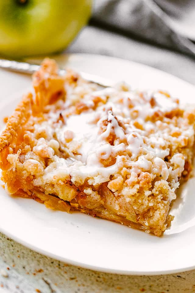 slice of apple slab pie on a white dessert plate set next to a green apple.