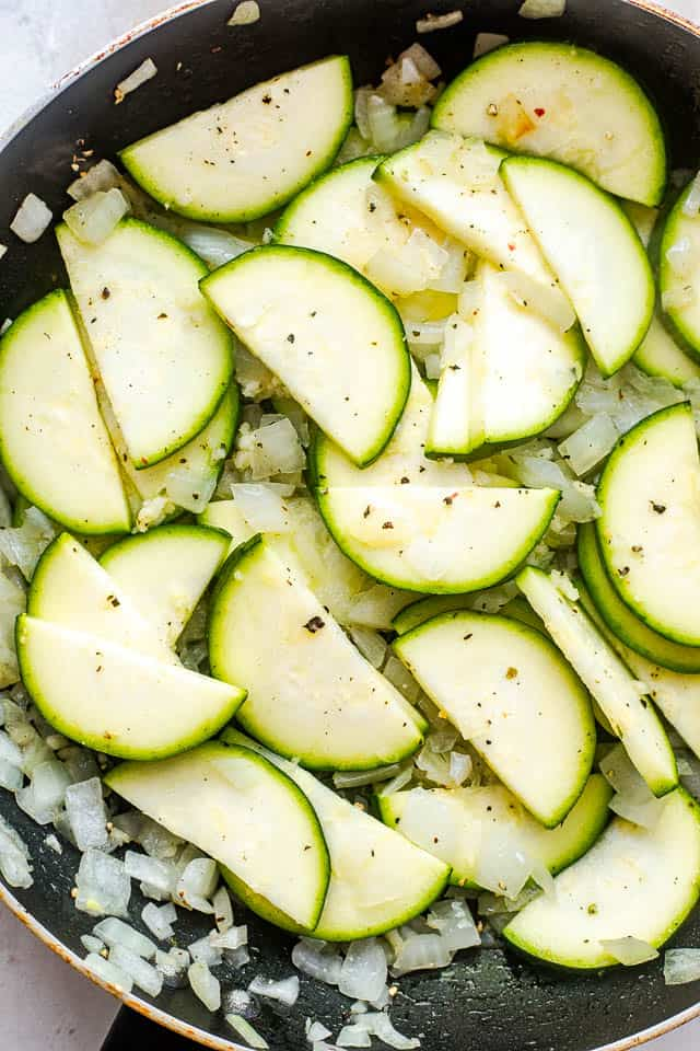 frying zucchini slices and diced onion in a black skillet