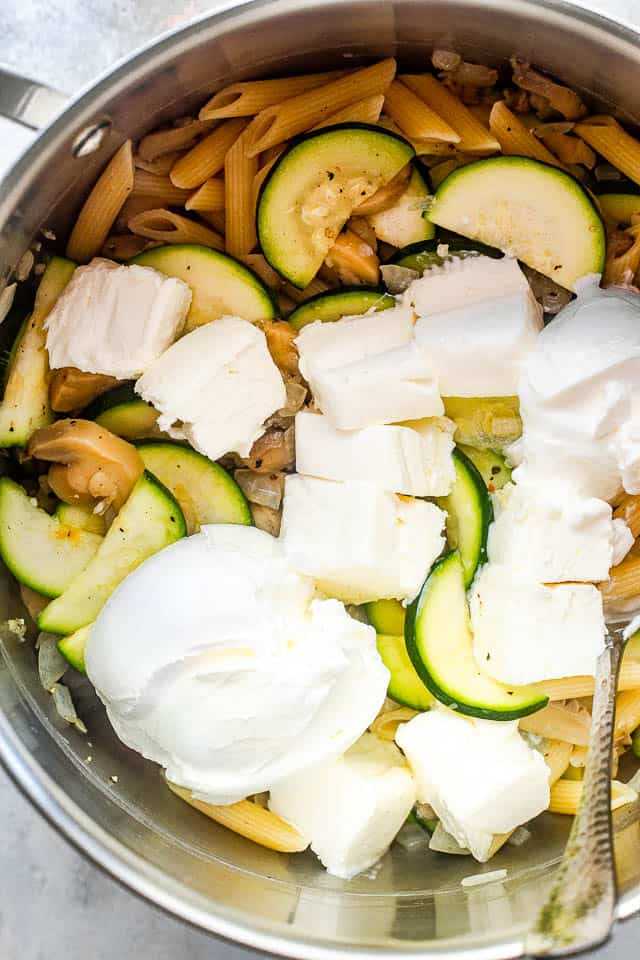overhead shot of a silver pot filled with pasta, zucchini slices, and cubed cream cheese