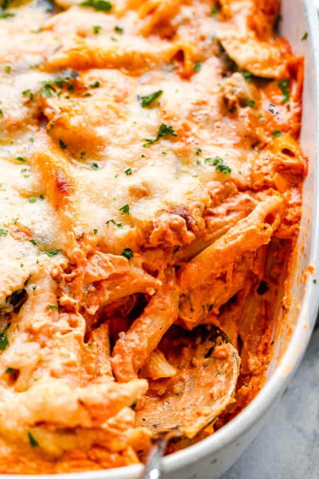 side view of a cheesy pasta in a baking dish with a serving spoon pulling out the food