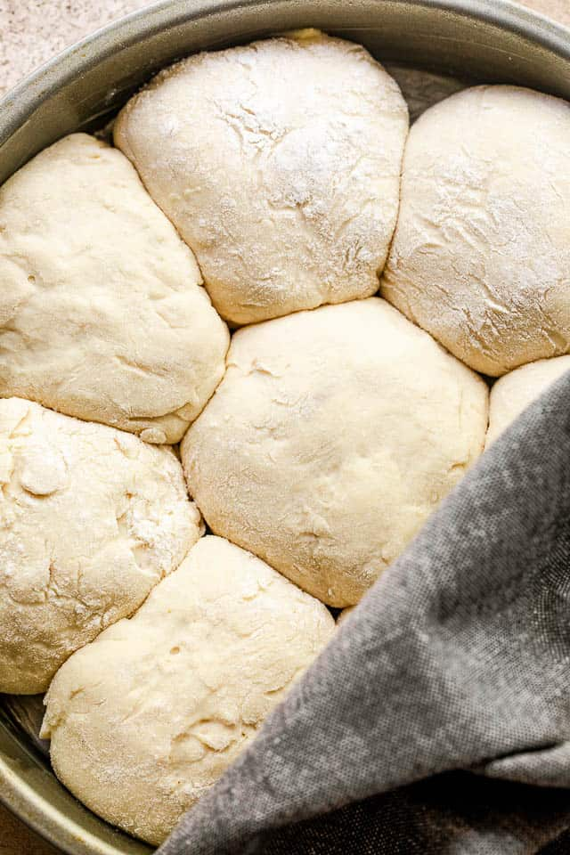 raw dinner rolls arranged in a cake pan and halfway covered with a grey kitchen towel