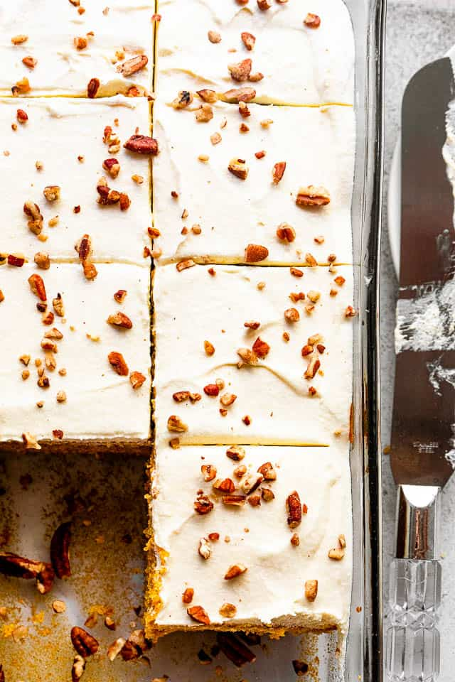 overhead shot of cream cheese frosted pumpkin cake sprinkled with chopped pecans