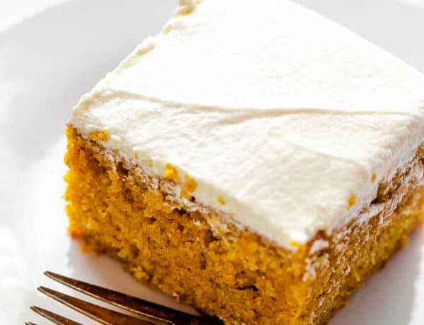 side shot of frosted pumpkin bar on a plate with a fork next to it