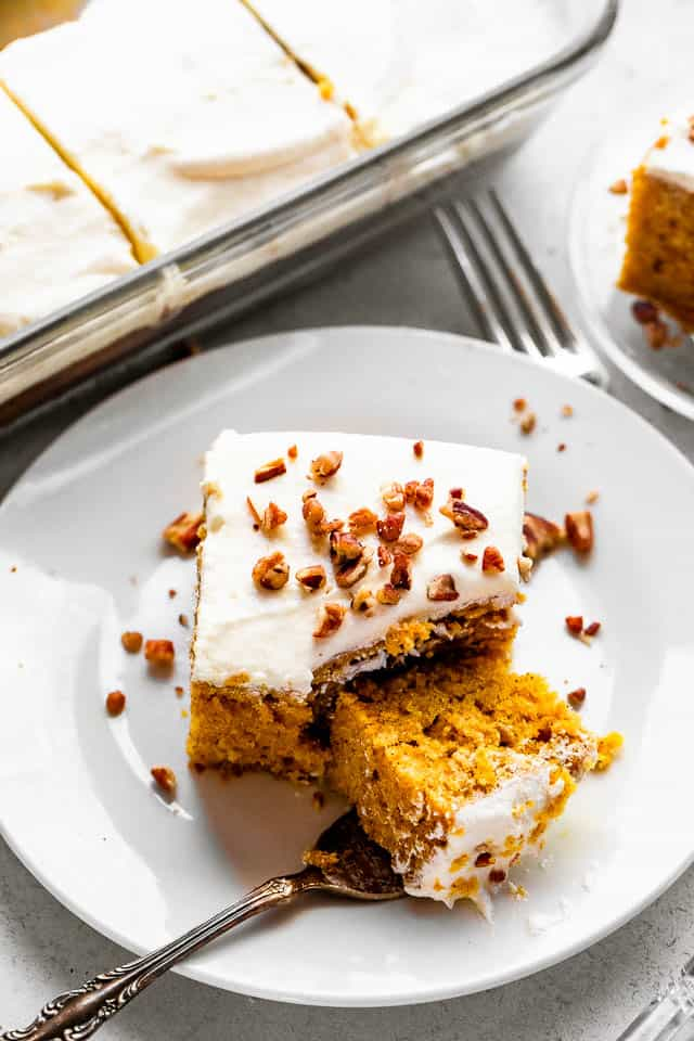 top shot of pumpkin bar slice topped with cream cheese frosting a chopped pecans