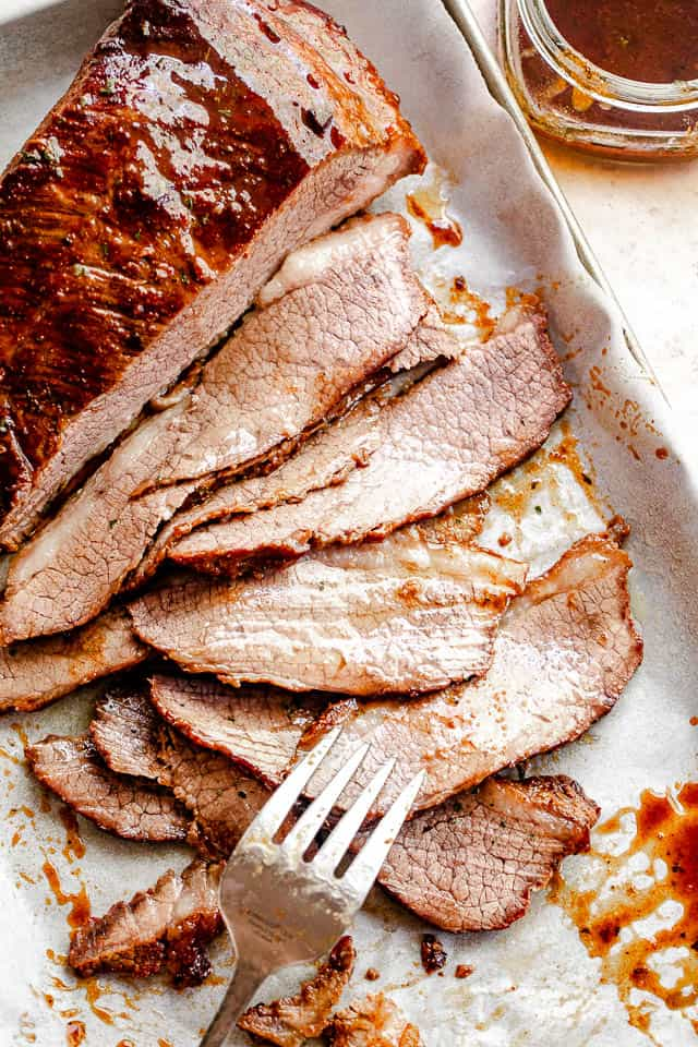 top view of sliced beef brisket with a silver fork placed at the bottom slice and a jar with barbecue sauce to the side