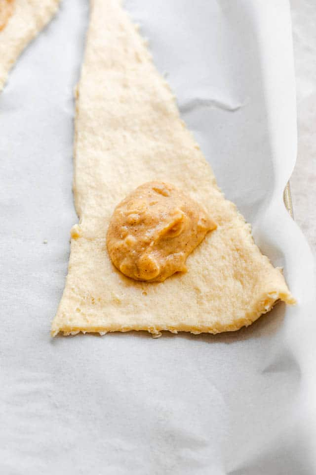 unrolled raw crescent dough with a dollop of pumpkin filling
