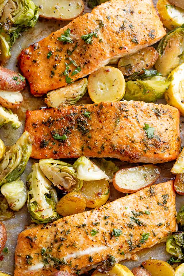 overhead shot of roasted old bay salmon fillets with brussel sprouts and yellow squash