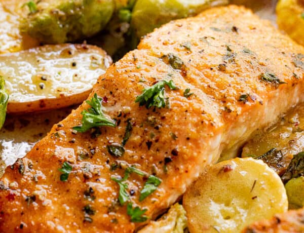 close up shot of roasted salmon fillets with brussel sprouts and yellow squash