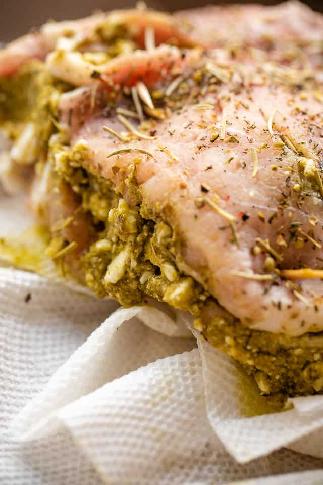 side shot of raw pork chop stuffed with pesto and feta cheese