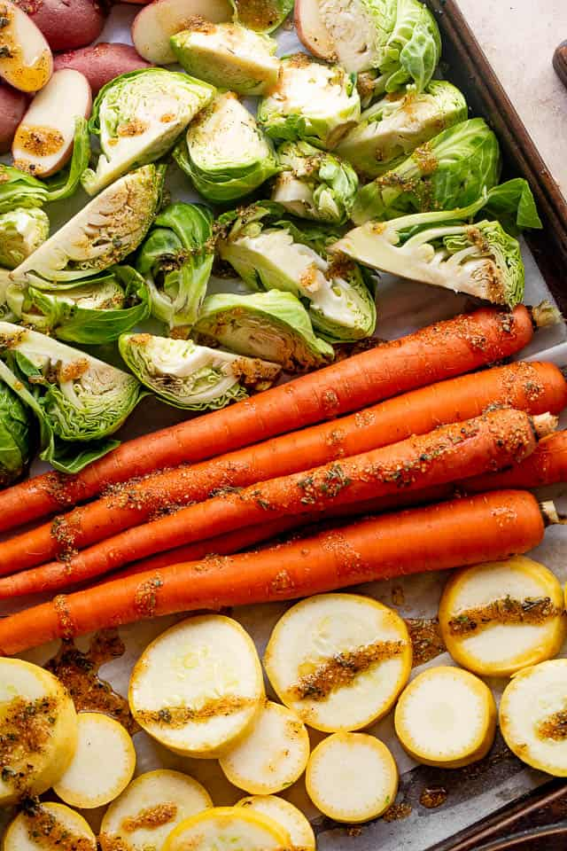 raw carrots, brussel sprouts, squash, and potatoes on a baking sheet