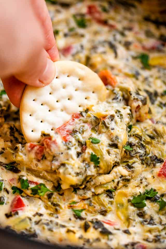 dipping a round cracker in spinach artichoke dip