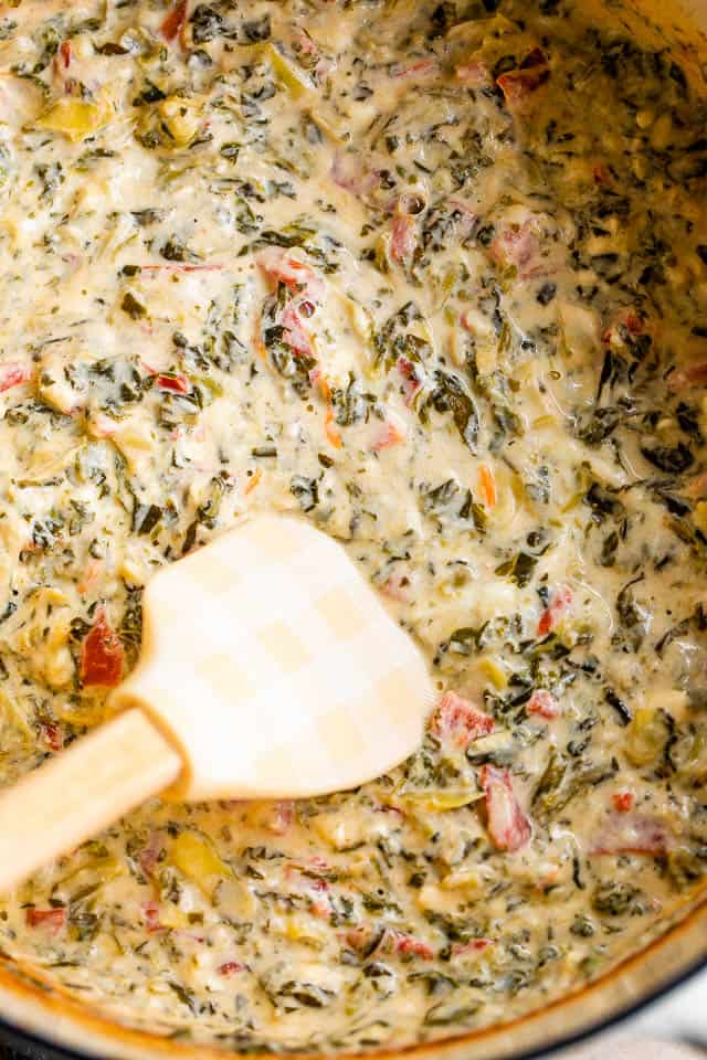 mixing spinach artichoke dip with a spatula