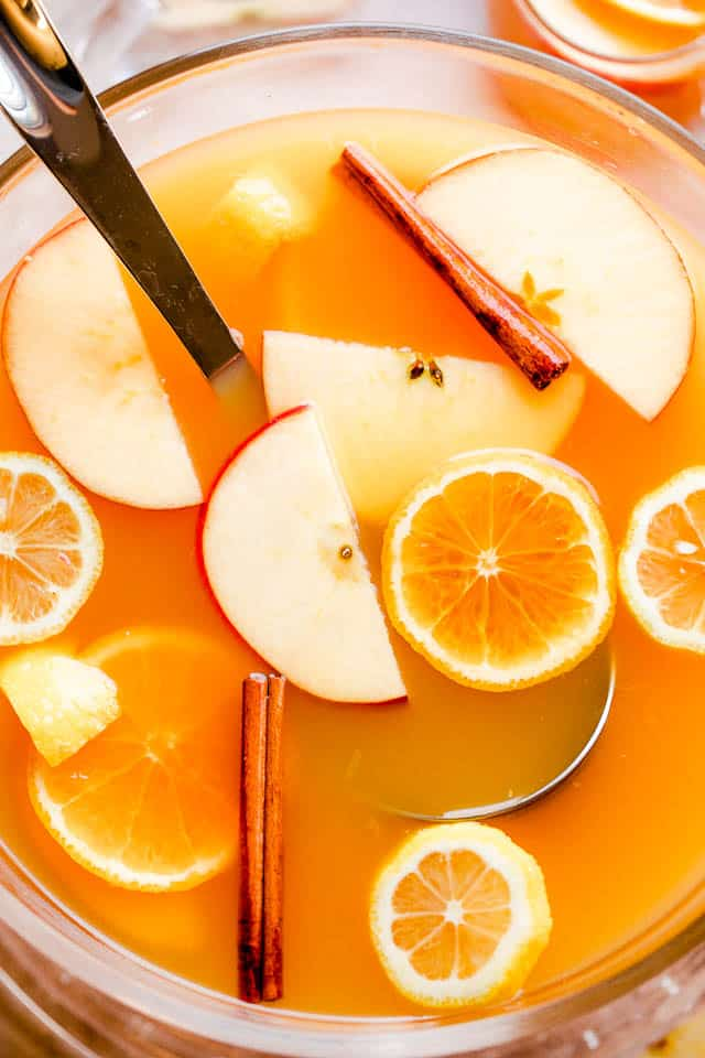 overhead shot of apple cider punch in a punch bowl with ladle and slices of fruit floating on top