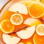 overhead close up shot of apple cider punch in a punch bowl with slices of fruit floating on top