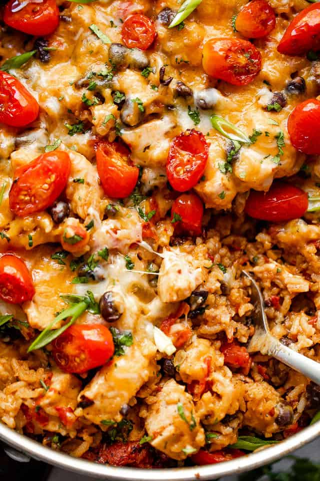 close up shot of chicken and rice burrito skillet topped with grape tomatoes