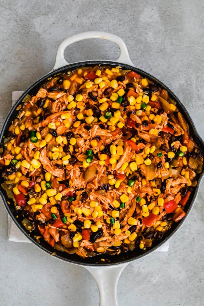 A Large Skillet Filled With A Hearty Chicken Enchilada Casserole