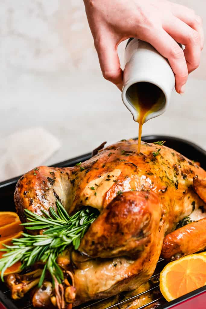 Basting a roasted turkey in a pan.