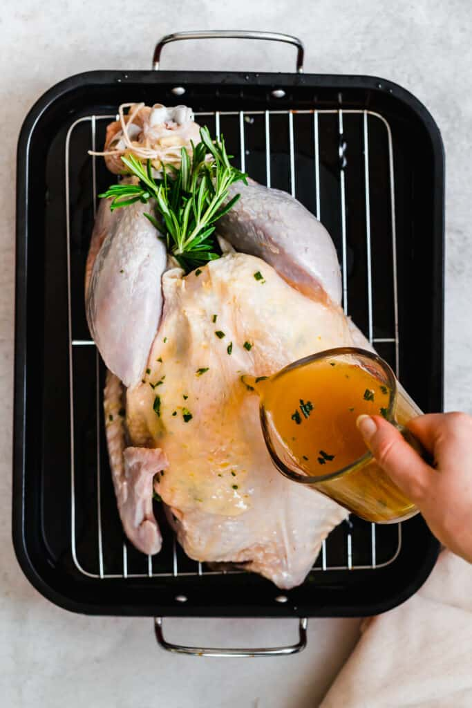 Uncooked turkey in a pan with broth being poured on top.
