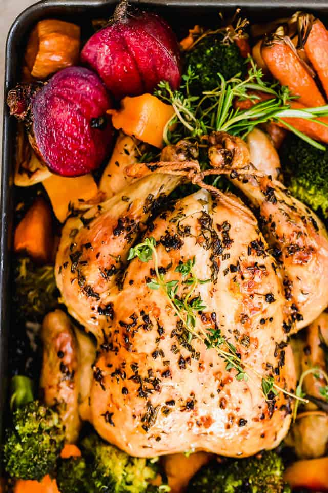 roasted chicken set over vegetables in a roasting pan