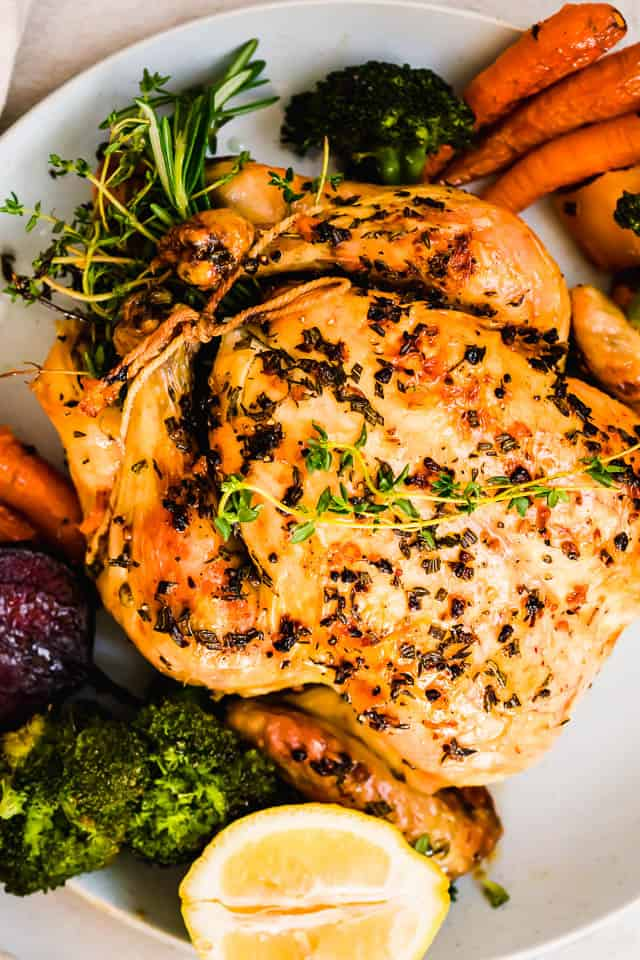 close up overhead shot of a whole chicken on a white serving platter with vegetables